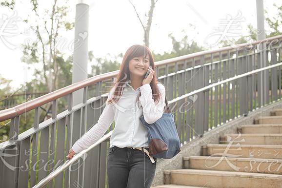 『電話しながら笑顔で階段を降りる女性』美人女性モデルの写真素材なら美scene
